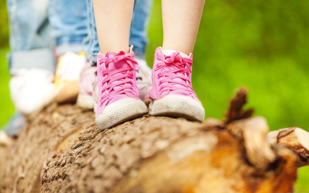 Children's feet in pink sneakers standing on a log
