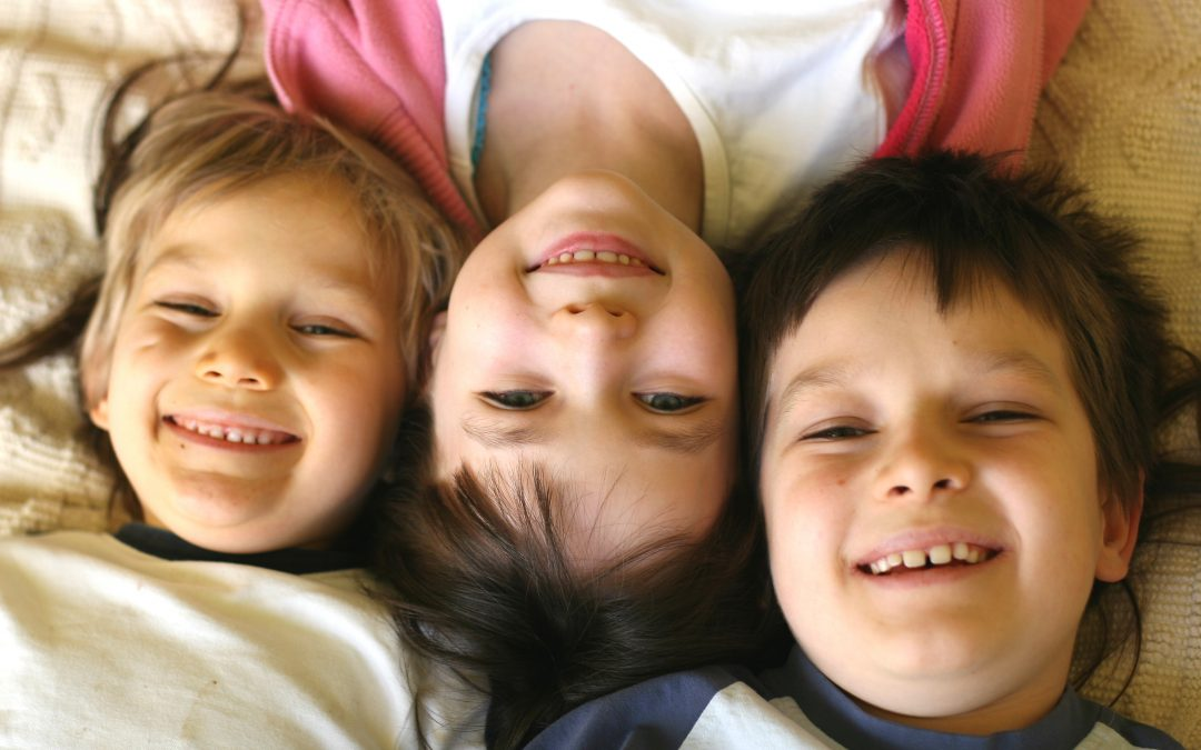 Three smiling children laying with their heads together