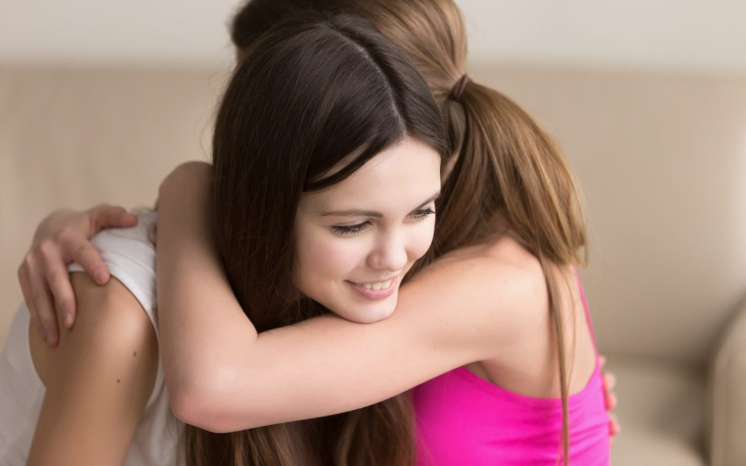 Two happy young women hugging when meeting