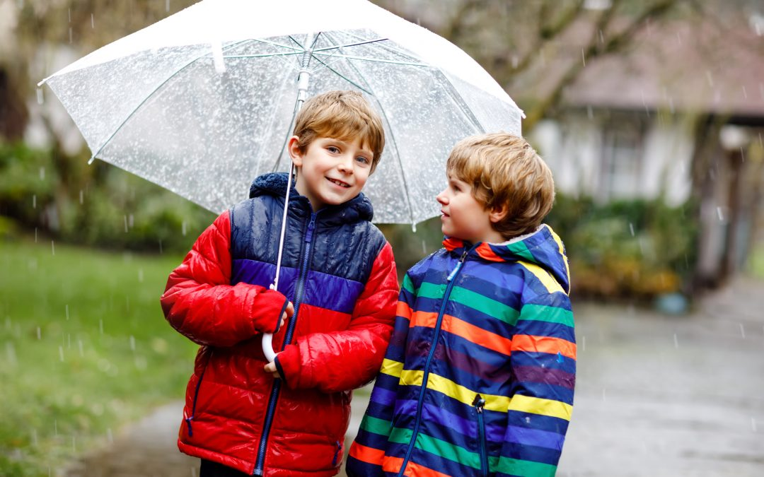 wo little kid boys on way to school walking during sleet, rain and snow with umbrella on cold day. Children, best friends and siblings in colorful fashion casual clothes