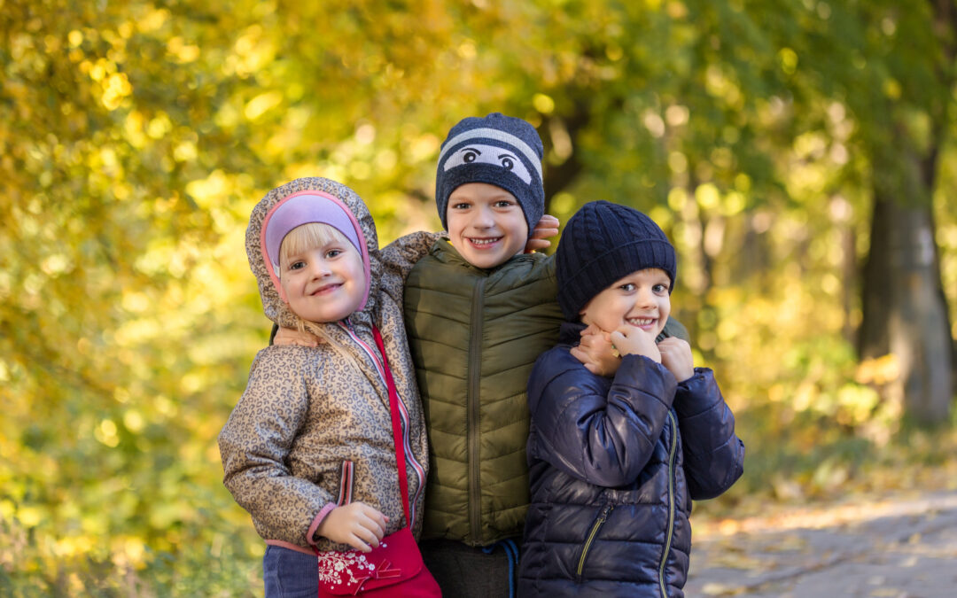 Group of happy three kids having fun outdoors in autumn park. Cute children enjoy hugging together against golden fall background. Best frend forever and happy childhood concept